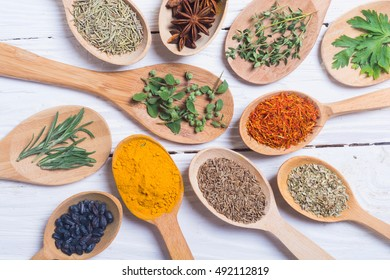 assortment of spices and herbs in spoon on wooden background