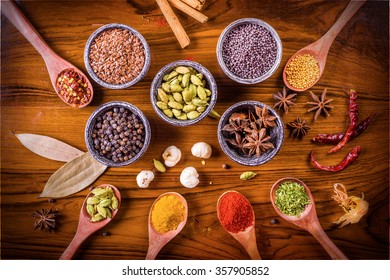 Assortment of spices and herbs in wooden spoons and stone spice bowls over polished textured wooden board.