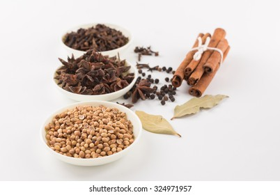 Assortment of spice,Star anise,coriander seed,clove in white bowls and pepper corn,bay leave,cinnamon over white background