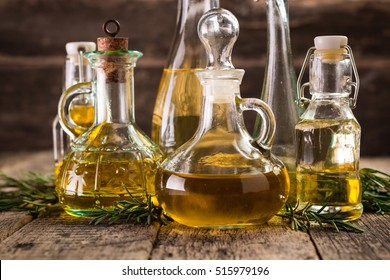 Assortment of spicy sunflower,corn,sesame seeds ,avocado ,grape seeds oils with herbs and spices in different bottles on wooden background