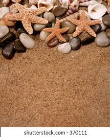 Assortment of starfish, seashells and smooth beach rocks in the sand - copy space