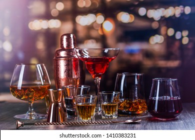 Assortment of strong alcohol drinks - margarita, cognac, vodka, red wine and tequila on a bar counter