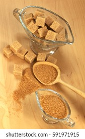 Assortment of sugar: brown cane sugar on the slices and brown sugar in containers , wooden spoon, on a light background, top view