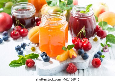 assortment of sweet jams and seasonal fruits on white table, closeup, horizontal