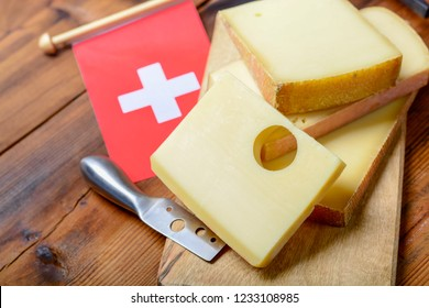 Assortment of Swiss cheeses Emmental or Emmentaler medium-hard cheese with round holes, Gruyere, appenzeller and raclette used for traditional cheese fondue and gratin and flag of Switzerland