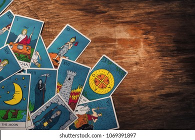 Assortment of Tarot inspired cards on a wooden background
