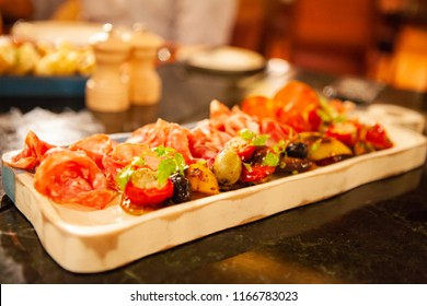 Assortment of tasty and delicious Italian antipasto. Prosciutto di Parma or Parma and Chorizo sausage with colorful grilled vegetable on a wooden board. A perfect appetizer and party snack. Warm Light