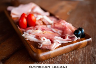 Assortment of tasty and delicious Italian Charcuterie antipasto delicatessen. Prosciutto di Parma or Parma ham, Salami sausage, Bologna on wooden board. Perfect appetizer or party snack. Natural light