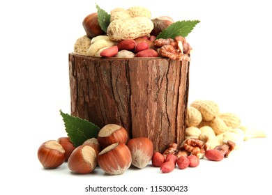 assortment of tasty nuts with leaves in wooden vase, isolated on white