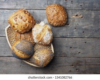 Assortment of tasty organic buns in a basket on a rustic kitchen table