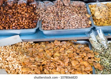 Assortment of tasty snacks at Ecuadorian street market, such as fried fava beans, salted almonds, glazed and toasted peanuts, etc.