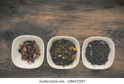 Assortment of tea in white bowls on a rustic wooden table