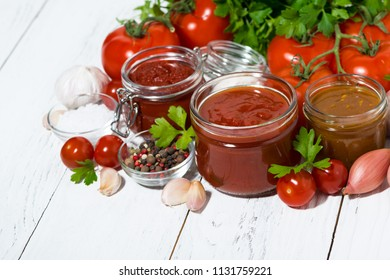 assortment of tomato sauces and ingredients on white background, top view