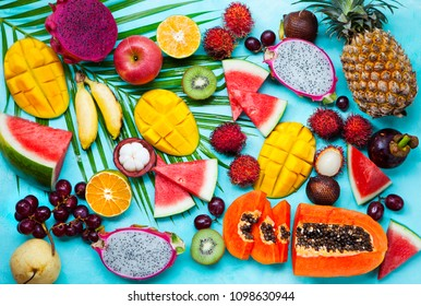 Assortment of tropical exotic fruits. Blue background. Top view.