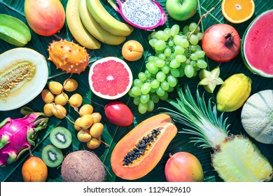 Assortment of tropical fruits on leaves of palm trees. Top view