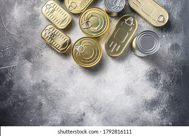 Assortment types of shapes canned food, fish , fruits, vegetables, meat, soup top view on grey rustic background top view space for text.