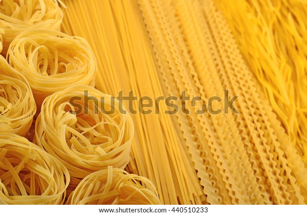 Assortment of uncooked Italian pasta close up as background