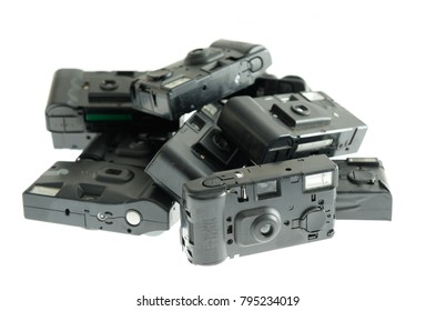 An assortment of used, dusty, disposable cameras. It is a collection of different brand objects, on white background. These products worked with 35 mm analog film.