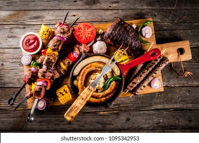 Assortment various barbecue food grill meat, bbq party fest - shish kebab, sausages, grilled meat fillet, fresh vegetables, sauces, spices, on old wooden rustic table, above copy space