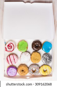 assortment of various colorful donuts in a white paper box , top view