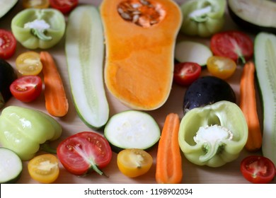 Assortment of various colorful vegetables: butternut squash, zucchini, cucumber, tomato, eggplant, pepper and carrot. Top view, selective focus.