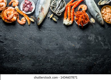 Assortment of various fresh seafood. On black rustic background