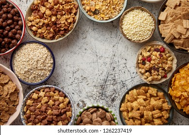 Assortment of various kinds cereals placed in ceramic bowls with cornflakes, granola, cereals and oatmeal. Flat lay, top view on white rusty table with copy space in the middle