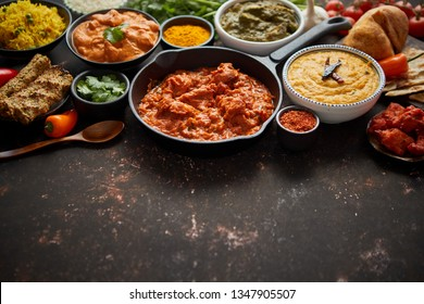 Assortment of various kinds of Indian cousine on dark rusty table. Chicken Tikka Masala, Butter, Nilgiri, Daal Tarka. Served with fried rice, naan bread and spices. Flat lay with copy space.
