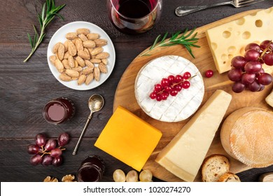 An assortment of various types of cheese with grapes, shot from above on a dark rustic background with a place for text