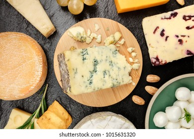 An assortment of various types of cheese, shot from above on a black background texture