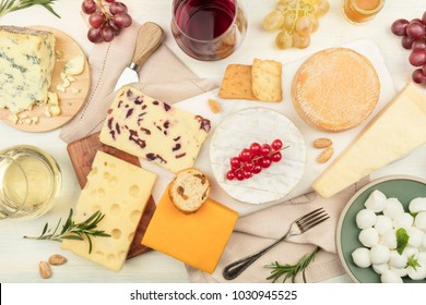 An assortment of various types of cheese with wine, shot from above on a light background