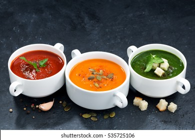 assortment of vegetable cream soup on a dark background, horizontal