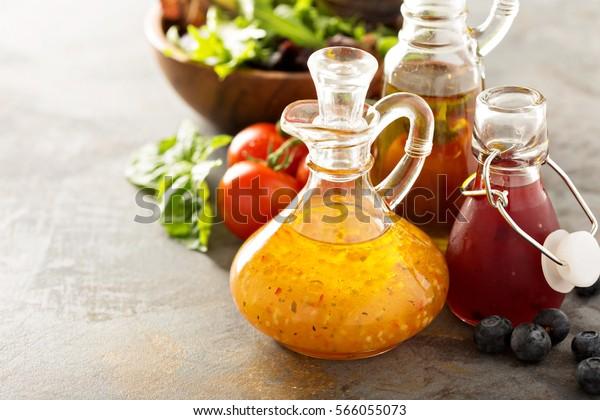 Assortment of vinaigrette salad dressings in glass bottles.