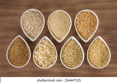 An assortment of whole grains in bowls over a wooden background