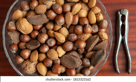 Assortment of whole nuts, walnuts, almonds, hazelnuts and Brazil nuts in a bowl with a nut cracker on a side, nutritious snack cracked and eaten in autumn or winter months as a special holidays treat.