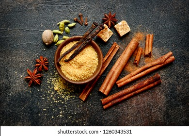 Assortment of winter spices : cinnamon, anise, cardamon, nutmeg, clove, vanilla and brown sugar on a dark slate, stone, concrete or metal background.Top view with copy space.