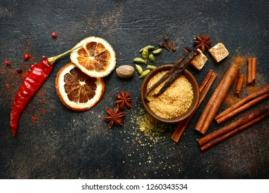 Assortment of winter spices : cinnamon, anise, cardamon, nutmeg, clove, vanilla , chili pepper and brown sugar on a dark slate, stone, concrete or metal background.Top view with copy space.