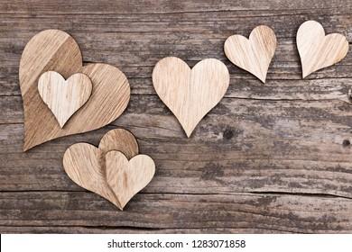 Assortment of wooden hearts on a wooden background