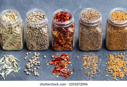 Assortments of spices, white pepper, chili flakes, lemongrass, cumin, fenugreek seeds in jars on grey stone background.
