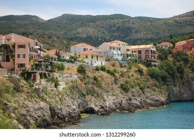 Assos, Kefalonia, Greece. Colorful houses of Assos village, beach and beautiful turquoise sea. Assos is a popular holiday destination on the tourists on Ionian island of Kefalonia.