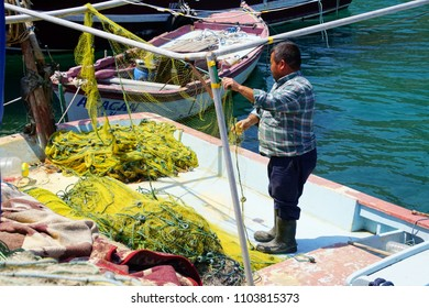 ASSOS, TURKEY - MAY 1, 2018 - Fisherman checking his nets on a small boat in the harbor of Behramkale Assos, Turkey