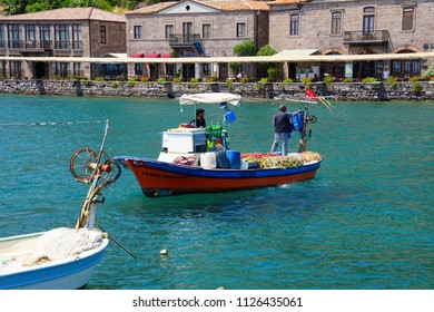 ASSOS, TURKEY - MAY 1, 2018 - Fisherman leaving harbor in their small boat in  Behramkale Assos, Turkey