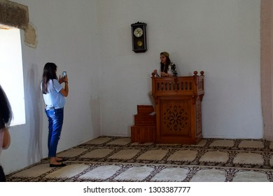 ASSOS, TURKEY - MAY 1, 2018 - Young woman photographs her friend on the imam's pulpit in small mosque, Behramkale Assos, Turkey