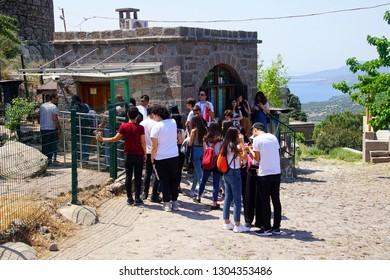 ASSOS, TURKEY - MAY 1, 2018 - Young people wait at the entrance to the temple ruins at Behramkale Assos, Turkey