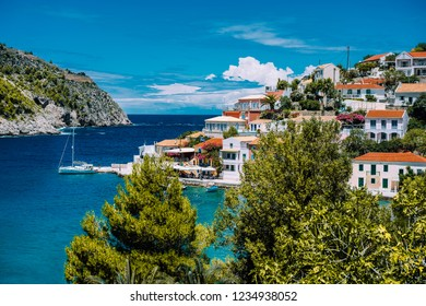 Assos village. Beautiful view to vivid colorful houses near blue turquoise colored transparent bay lagoon with yacht ship. Kefalonia, Greece