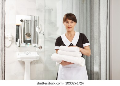 I assure you will have great time in our hotel. Portrait of pleasant caucasian woman working as housemaid, holding towels while standing near bathroom and staring at camera. I put them near shower