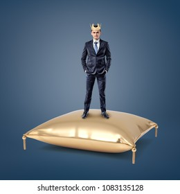 An assured businessman wearing a golden crown stands on a golden cushion. Privileged status. Financial king. Top manager.