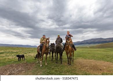 ASSY PLATEAU, KAZAKHSTAN - SEPTEMBER  2, 2016: Kazakh nomadic horsemen smile and look at me in the Assy Plateau in Kazakhstan.