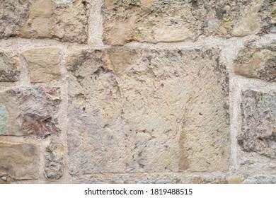Assymetric masonry of different size natural stone blocks. Wall