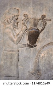 The Assyrian bearded man holds an ornate jug of wine in his hands. Ancient relief on the wall of the ruined city of Persepolis. Persepolis. Iran.